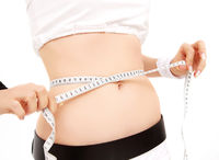 woman measuring her belly on white background