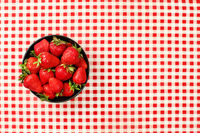Tabletop view, small black ceramic bowl of strawberries on red chequered gingham tablecloth
