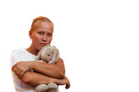 Young girl hugs a toy hare and looks at the camera