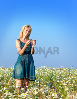 The beautiful happy young woman in the field of chamomiles guesses on a chamomile