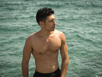 Athletic young man standing in ocean water, shirtless, looking away