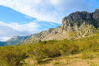 Autumn mountain landscape-rocky stone mountains covered with green bushes illuminated by the sun against a blue sky with white clouds
