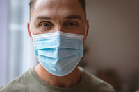 Close up view of caucasian man wearing face mask at home