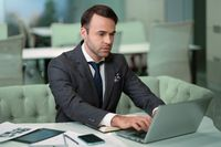Freelancer sitting in front laptop in bright coworking space. Handsome man in business suit working on laptop, freelancer job in progress