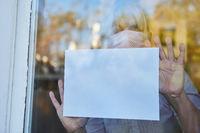 Seniorin in Quarantäne hält leeren Zettel an Fenster