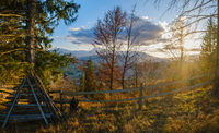 Late autumn mountain pre sunset scene with snow covered tops in far. Picturesque traveling, seasonal, nature and countryside beauty concept scene. Carpathians, Ukraine.