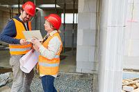 Handwerker und Architektin auf der Rohbau Baustelle