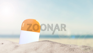 Sunscreen bottle in sand on beach with place for text
