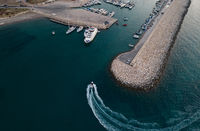 Aerial view of speedboat entering the harbor yachts moored at the marina. Latsi harbor Paphos Cyprus