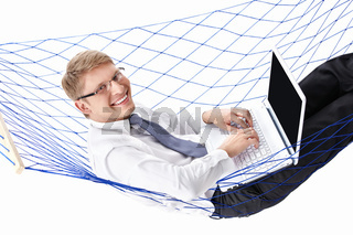 Businessman in a tie with a laptop in a hammock isolated