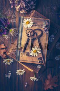 Key to knowledge concept. Old keys on a vintage book with flowers on wooden background.