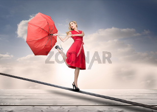 Pretty woman with a broken umbrella over the clouds