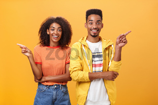 Which one telling true. Joyful and friendly good-looking couple, african american woman pointing left and dark-skinned guy right smiling broadly at camera giving advices but disagree with each other