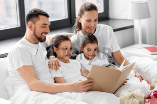 happy family reading book in bed on christmas