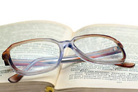 reading glasses lying on the book isolated on whit