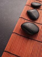 Three massage stones on a bamboo mat