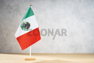 Mexico table flag on white textured wall. Copy space for text, designs or drawings