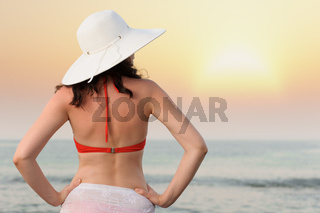 The woman on sea coast in a hat. Sunset illumination.