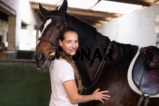 Portrait of smiling female jockey standing by horse