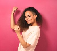 Happy and excited expressing winning gesture young African American girl looking positively at camera wearing peachy t-shirt isolated on pink background. Beauty concept. Square crop