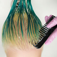 High-angle shot of hairstylist combing wet green and discolored hair while shampooing in sink