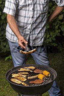 Mann hält eine Wurst am Grill