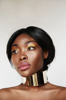 Vertical headshot of young black woman with golden make-up, posing in the studio