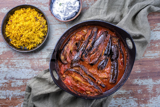Modern style slow cooked Persian lamb eggplant stew khoresh bademjan served with rice and yoghurt as top view in a design pot