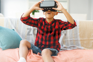 Smiling asian boy sitting on couch and using vr headset