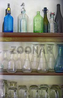 Regal mit alten leeren Flaschen und Gläsern