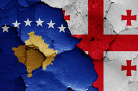 flags of Kosovo and Georgia painted on cracked wall