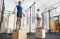 Two man jumping on fit box at gym.