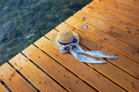 The concept of a vacation at the sea on a wooden pier is a hat, sunglasses, a glass of wine, top view.
