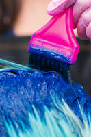 Hairdresser applying blue paint to female with emerald hair color during process of dyeing hair in stylish color