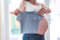 Happy pregnant mother is holding little blue baby shirt