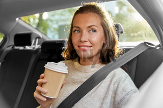 smiling woman or passenger drinking coffee in car