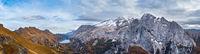 Autumn Dolomites mountain scene from hiking path betwen Pordoi Pass and Fedaia Lake, Italy. Snowy Marmolada Glacier and Fedaia Lake in far.