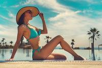 Woman wear bikini and hat relaxing on edge of pool