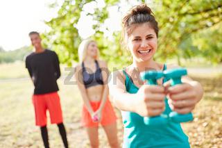 Frau im Fitness Kurs beim Training mit Kurzhanteln