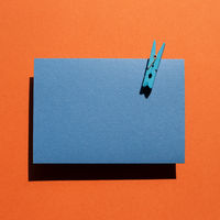 Blue memo pad with wooden clip on red background. top view, copy space