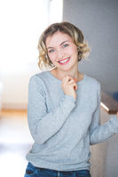 Beautiful blonde woman with curly hair is confidentially smiling, positive emotion