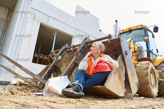 Frau als Bauarbeiter in Schaufel vom Bagger zur Pause