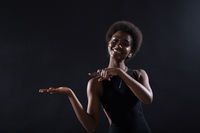 Empty female hand of african american woman holding on black background