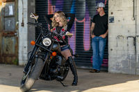 A Lovely Blonde Model Poses Outdoors With Her Motorcycle In A Large City Environment