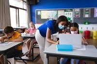 African american female teacher wearing face mask teaching a girl to use laptop at elementary school