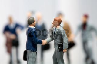 Geschäftsmänner schütteln Hände bejubelt von ihrem Team
