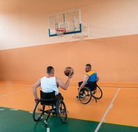 a cameraman with professional equipment records a match of the national team in a wheelchair playing a match in the arena