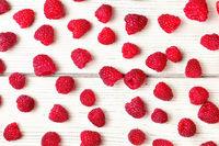 Tabletop view, raspberries spilled on white boards desk.