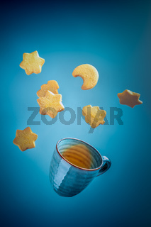 Cookies and tea, flying on a dark blue background