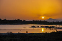 Sunset at the Larnaca salt lake witht he setting sun and wind turbines in the distance